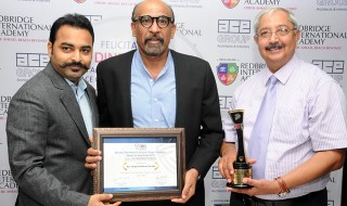 """Mr. Dinesh Verma, Principal Architect and Managing Director, ACE Group Architects, showcasing """"Best Institutional Architecture Award"""" he received during the Second BERG Real Estate Awards in Singapore for designing Redbridge International Academy, Bangalore. Chairman of Redbridge International Academy Mr. Rohan Agarwal (Left) and Principal of Redbridge International Academy Mr. Christopher Anthony Browne (Right) also seen during the occasion."""